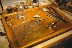 Gruppo di lavoro degli orologisti con l'orologio che ripara gli strumenti Immagini Stock