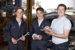 Gruppo di lavoro del garage di Teaching Trainees In del meccanico Fotografia Stock