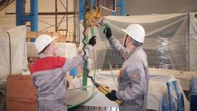 Gruppo di lavoro di fabbricazione I lavoratori regola la macchina nel magazzino la produzione di ventilazione e delle grondaie St stock footage