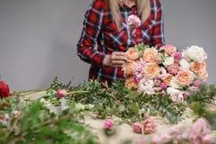 Gruppo di lavoro femminile di Floral del fiorista - donna che rende ad una bella composizione nel fiore un mazzo Concetto di Flor immagine stock