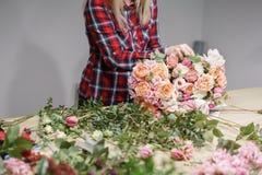 Gruppo di lavoro femminile di Floral del fiorista - donna che rende ad una bella composizione nel fiore un mazzo Concetto di Flor fotografia stock libera da diritti