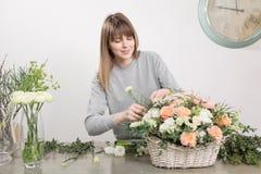 Gruppo di lavoro femminile sorridente di Floral del fiorista - donna che rende ad una bella composizione nel fiore un mazzo in un immagine stock