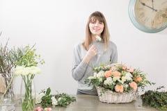 Gruppo di lavoro femminile sorridente di Floral del fiorista - donna che rende ad una bella composizione nel fiore un mazzo in un immagine stock libera da diritti