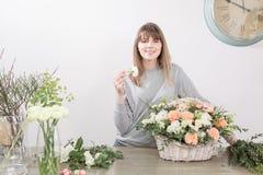 Gruppo di lavoro femminile sorridente di Floral del fiorista - donna che rende ad una bella composizione nel fiore un mazzo in un fotografie stock libere da diritti