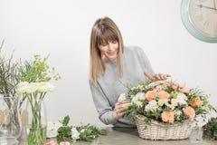 Gruppo di lavoro femminile sorridente di Floral del fiorista - donna che rende ad una bella composizione nel fiore un mazzo in un fotografia stock libera da diritti