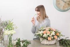 Gruppo di lavoro femminile sorridente di Floral del fiorista - donna che rende ad una bella composizione nel fiore un mazzo in un immagini stock libere da diritti