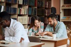 Gruppo di libri e di preparazione di lettura felici degli studenti all'esame in biblioteca immagini stock