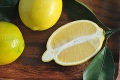 Gruppo di limoni gialli con le foglie sul piatto di legno Fotografia Stock