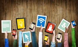 Gruppo di mani che tengono i dispositivi di Digital con i simboli illustrazione di stock