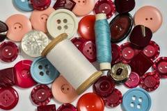 Gruppo di manopole multicolori e bobine del filo per cucire Fotografie Stock