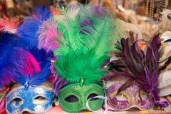 Gruppo di maschere variopinte di carnevale, isolato sul contatore di vendita Fotografie Stock