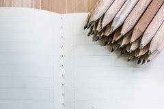 Gruppo di matita messo sul taccuino vuoto Immagini Stock