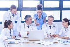Gruppo di medici che esamina computer portatile e che ha una discussione fotografie stock libere da diritti