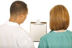 Gruppo di medici che esamina la scheda di clip Fotografia Stock