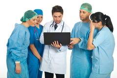 Gruppo di medici che per mezzo del computer portatile Immagini Stock