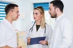 Gruppo di medici che sta e che parla all'ospedale immagini stock