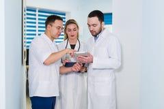 Gruppo di medici che sta e che parla all'ospedale immagini stock libere da diritti