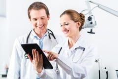 Gruppo di medici in clinica con il computer della compressa Fotografia Stock