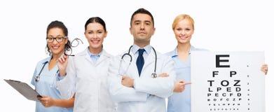 Gruppo di medici con il grafico ed i vetri di occhio fotografia stock libera da diritti