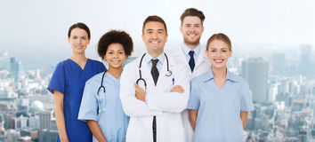 Gruppo di medici felici sopra fondo blu Immagine Stock