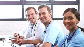 Gruppo di medici sorridente in una riunione video d archivio
