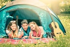 Gruppo di migliori amici con i pollici su in tenda di campeggio Fotografia Stock Libera da Diritti
