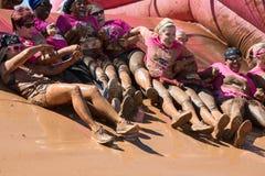Gruppo di Muddy Women Hold Hands Sliding nel pozzo del fango Fotografie Stock Libere da Diritti