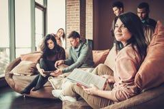 Gruppo di multi giovani studenti etnici che preparano per gli esami nell'interno domestico Fotografia Stock Libera da Diritti