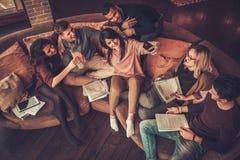 Gruppo di multi giovani studenti etnici che preparano per gli esami nell'interno domestico Fotografie Stock
