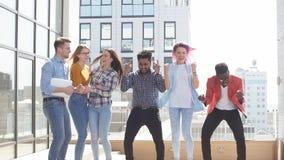 Gruppo di multi giovanotti etnici che raffreddano nel fondo all'aperto urbano archivi video