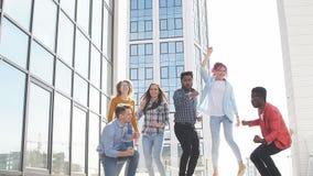 Gruppo di multi giovanotti etnici che raffreddano nel fondo all'aperto urbano video d archivio