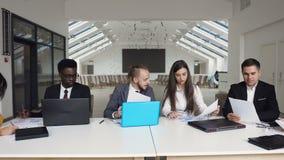 Gruppo di multi riuscita gente di affari etnica che si siede alla segnalazione della società verificata tavola dell'ufficio nei d video d archivio