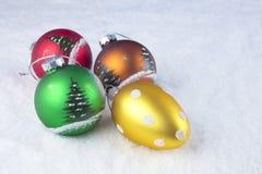 Gruppo di palle variopinte di Natale su un fondo bianco della neve Immagini Stock