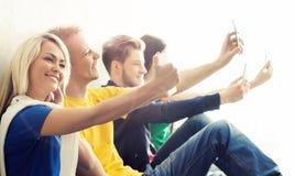 Gruppo di pantaloni a vita bassa che prendono selfie Studenti su una rottura Immagini Stock Libere da Diritti