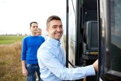 Gruppo di passeggeri maschii felici che si imbarcano sul bus di viaggio Immagini Stock
