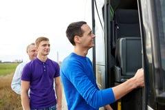 Gruppo di passeggeri maschii felici che si imbarcano sul bus di viaggio Fotografie Stock Libere da Diritti