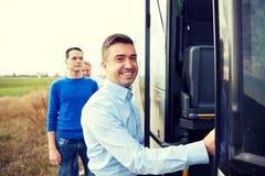 Gruppo di passeggeri maschii felici che si imbarcano sul bus di viaggio Fotografia Stock Libera da Diritti