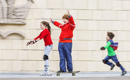 Gruppo di pattinaggio a rotelle dei bambini in parco pubblico Fotografia Stock