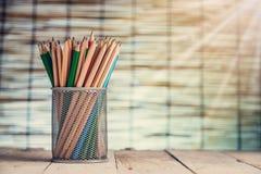 Gruppo di penne e di matite di legno in vaso del metallo Fotografia Stock