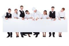 Gruppo di personale di approvvigionamento che tiene un'insegna in bianco Immagine Stock