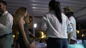Gruppo di persone ad un partito che balla e che si diverte in un night-club video d archivio