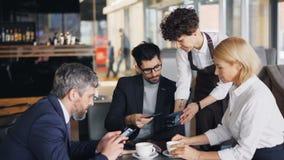 Gruppo di persone di affari che pagano il pranzo in caffè facendo uso dello smartphone moderno video d archivio