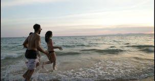 Gruppo di persone allegro che corrono insieme nel mare, amici felici della corsa della miscela sul divertiresi della spiaggia archivi video