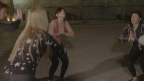Gruppo di persone che allungano e che fanno i pilates in un posto sotterraneo di freddo fatto di sale - stock footage