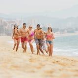 Gruppo di persone che corrono alla spiaggia del mare Fotografia Stock
