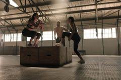 Gruppo di persone che fanno allenamento di salto della scatola in palestra Fotografie Stock
