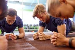 Gruppo di persone che fanno esercizio della plancia in palestra Fotografia Stock Libera da Diritti