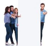 Gruppo di persone che fanno il segno giusto mentre presentando bordo Fotografia Stock