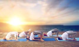 Gruppo di persone che fanno posa del ponte di yoga all'aperto Immagine Stock