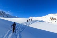 Gruppo di persone che fanno un'escursione sulle racchette da neve e sul panorama della neve della montagna con cielo blu nelle al Fotografia Stock Libera da Diritti